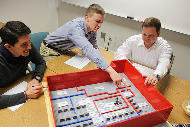Sergio Viscarra, Jabel Warren and Steven Prigg present their team's LEGO model of the proposed floor layout to the ENCS inventory team at a status meeting this semester.