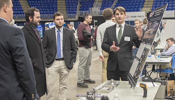 a student explains his project to a showcase attendee